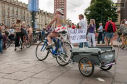 Ciclonudista con cartello per comunicare il messaggio dell'iniziativa WNBR