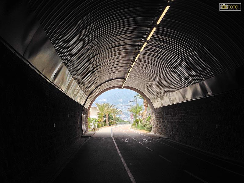 Al termine del tunnel palme e mare azzurro attendono i ciclisti