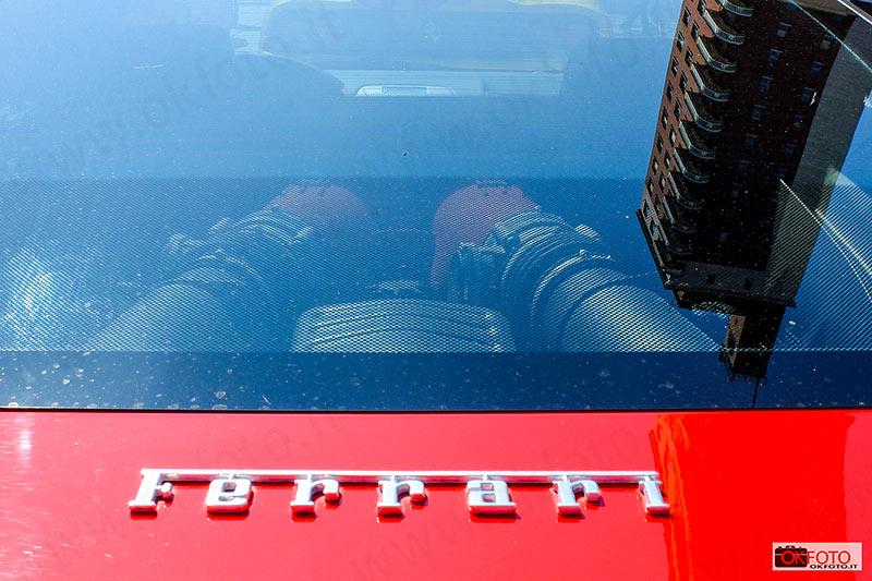 La torre della Reale Mutua si riflette su una Ferrari